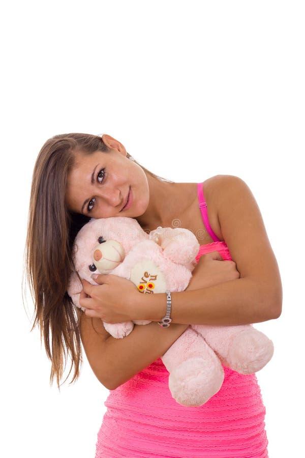 Jovem mulher bonita que guarda o urso de peluche e que abraça o que sorri imagem de stock
