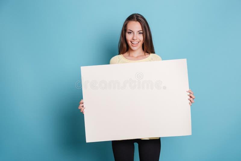 Jovem mulher bonita que guarda a placa vazia vazia sobre o fundo azul imagens de stock