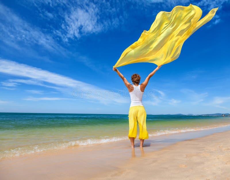 Jovem mulher bonita que guarda a tela amarela no vento fotografia de stock royalty free
