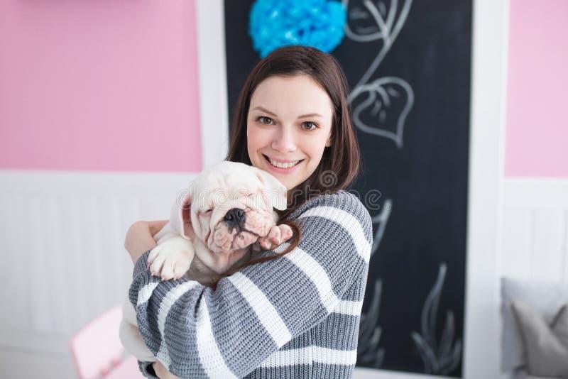 Jovem mulher bonita que guarda um buldogue do inglês do cachorrinho foto de stock