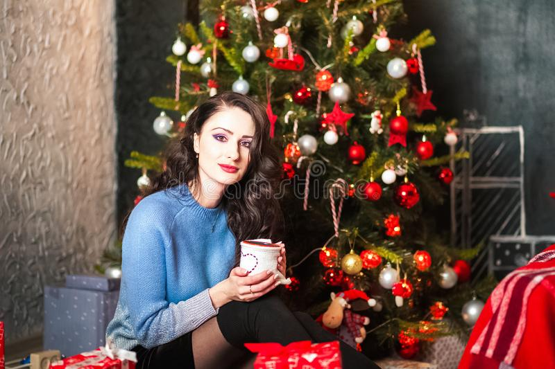 Jovem mulher bonita que guarda um copo nas mãos de uma árvore do ano novo Morena no quarto decorado para o Natal fotografia de stock