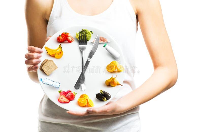 Jovem mulher bonita que guarda uma placa com alimento, conceito da dieta imagens de stock