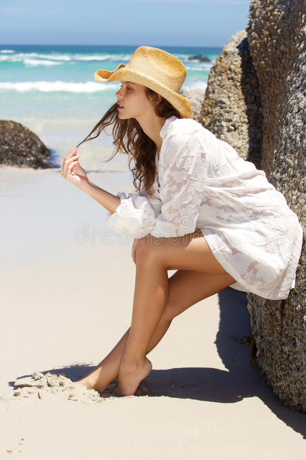 Jovem mulher bonita que inclina-se contra a rocha na praia imagens de stock royalty free