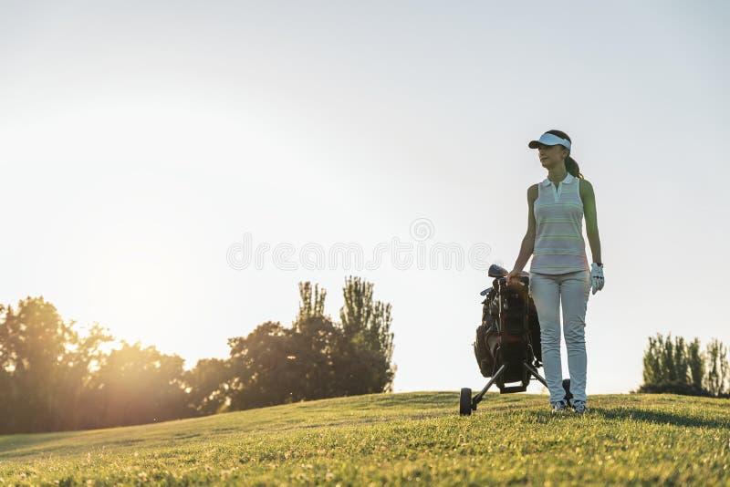 Jovem mulher bonita que joga o golfe imagens de stock