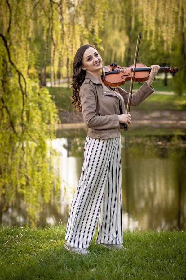 Jovem mulher bonita que joga o violino no parque e nos sorrisos, retrato completo fotos de stock