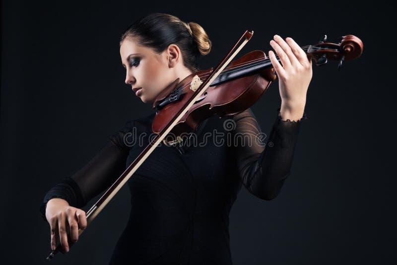 Jovem mulher bonita que joga o violino sobre o preto imagens de stock royalty free