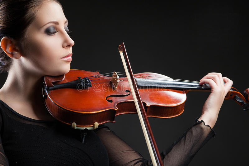 Jovem mulher bonita que joga o violino sobre o preto fotografia de stock