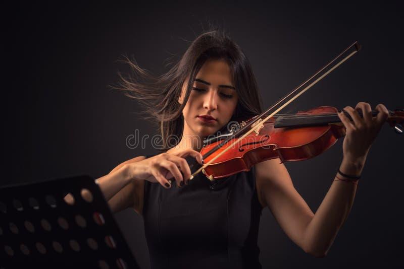 Jovem mulher bonita que joga um violino sobre o fundo preto fotografia de stock royalty free