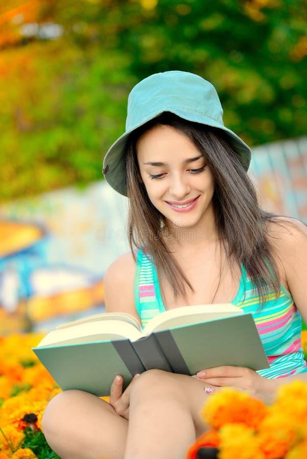 Jovem mulher bonita que lê um livro fora imagem de stock royalty free