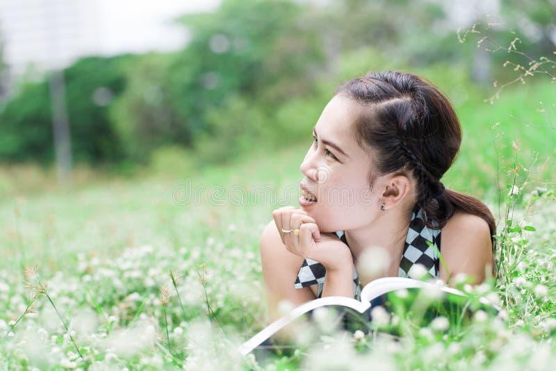Jovem mulher bonita que lê um livro na natureza foto de stock