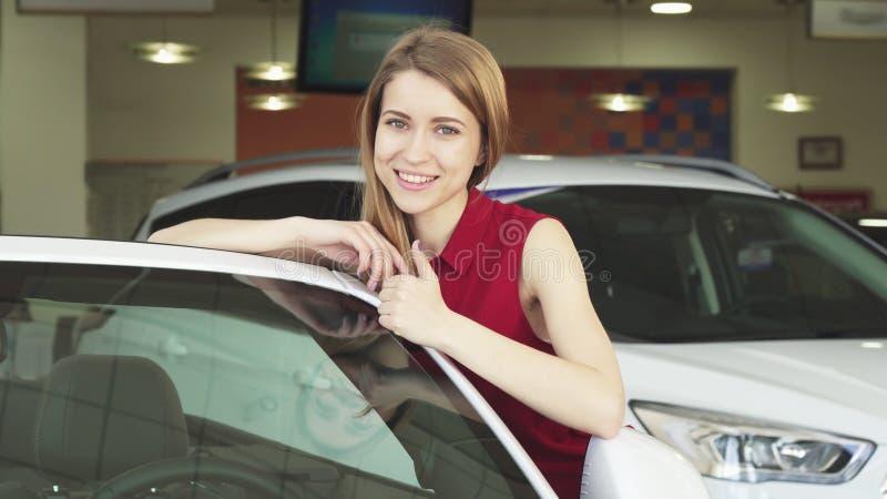 Jovem mulher bonita que levanta com um automóvel novo no negócio foto de stock royalty free