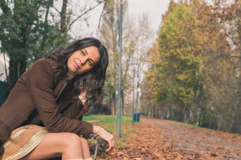 Jovem mulher bonita que levanta em um parque da cidade fotos de stock royalty free