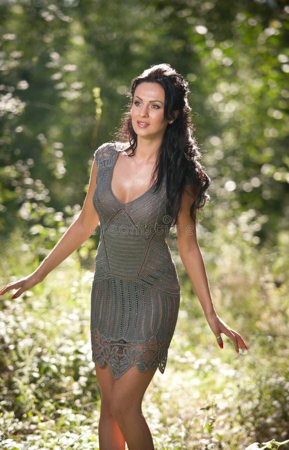 Jovem mulher bonita que levanta em um prado do verão Retrato da menina moreno atrativa com o cabelo longo que relaxa na natureza, fotografia de stock