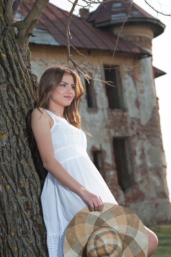 Jovem mulher bonita que levanta na frente da exploração agrícola. Menina loura muito atrativa com o vestido curto branco que guard imagens de stock royalty free