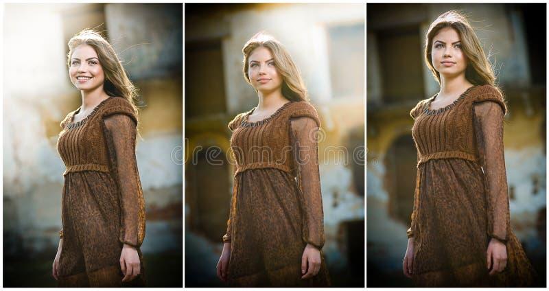 Jovem mulher bonita que levanta na frente da exploração agrícola. Menina loura muito atrativa com o vestido curto marrom. Levantam fotos de stock royalty free