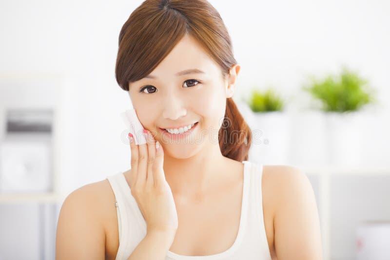 Jovem mulher bonita que limpa sua cara com o algodão imagem de stock