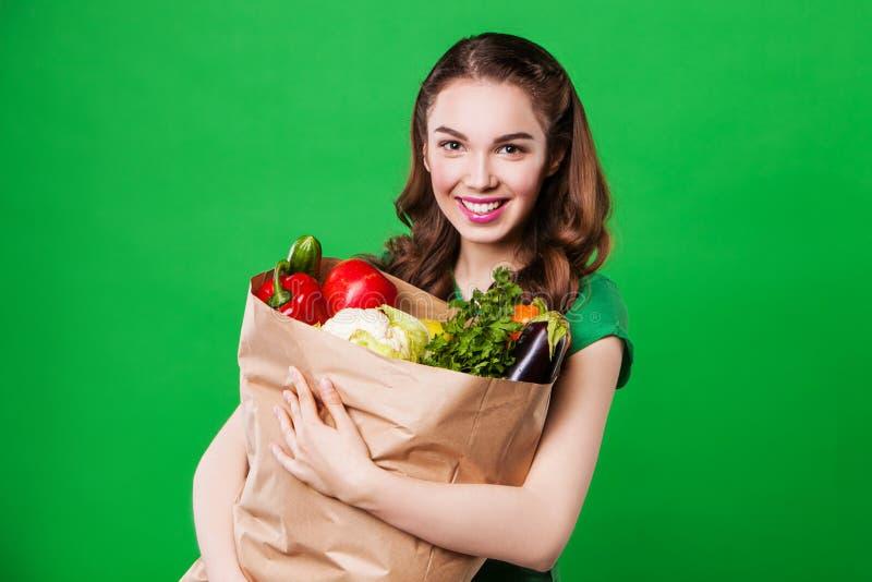 Jovem mulher bonita que mantém um saco de mantimento completo imagens de stock