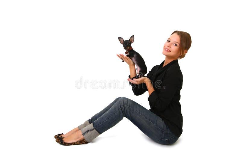 Jovem mulher bonita que mantem um cão pequeno bonito isolado fotos de stock royalty free