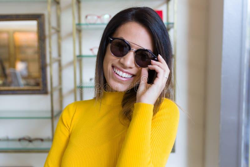 Jovem mulher bonita que mostra seus óculos de sol novos ao olhar a câmera na loja ótica foto de stock