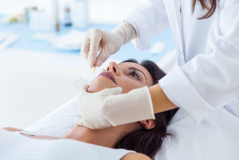 Jovem mulher bonita que obtém a botox a injeção cosmética em sua cara imagens de stock royalty free