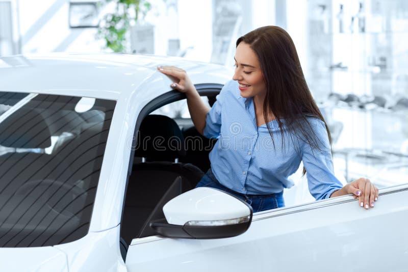 Jovem mulher bonita que obtém em um carro novo fotos de stock royalty free