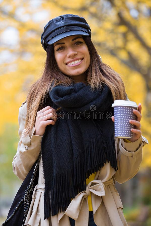 Jovem mulher bonita que olha a câmera ao andar através do parque no outono imagens de stock royalty free