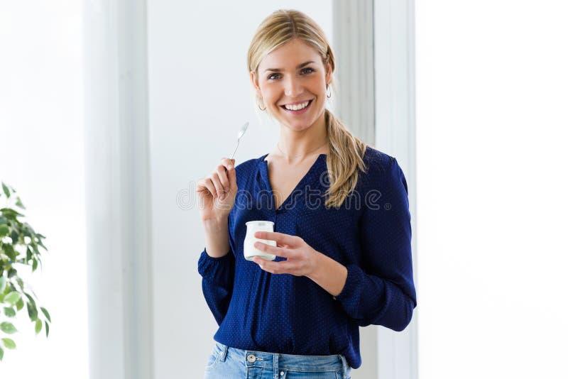 Jovem mulher bonita que olha a câmera ao comer o iogurte em casa foto de stock