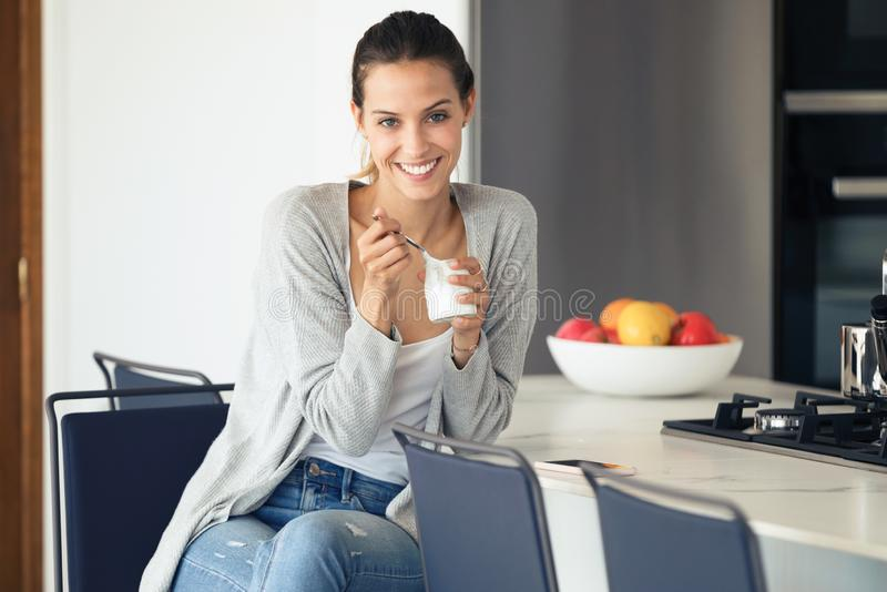 Jovem mulher bonita que olha a câmera ao comer o iogurte na cozinha em casa fotos de stock royalty free