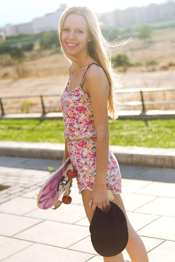 Jovem mulher bonita que olha a câmera com skate fotografia de stock royalty free