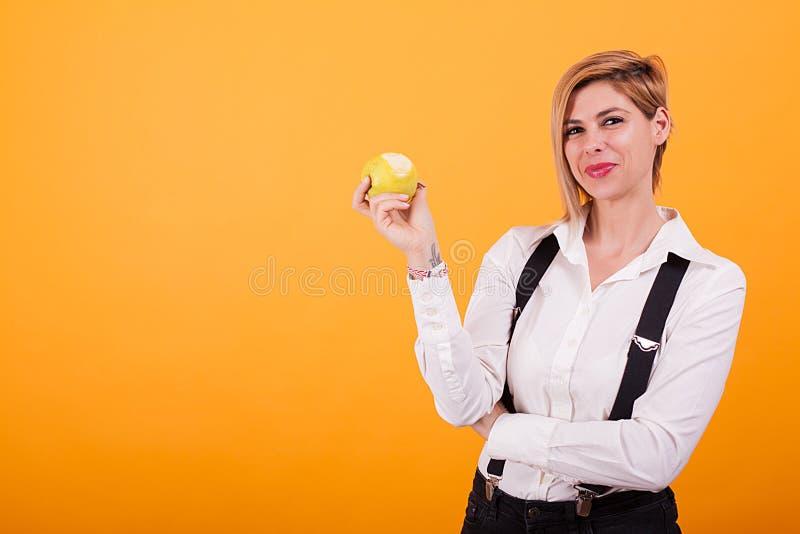 Jovem mulher bonita que olha a câmera e que guarda uma maçã verde mordida sobre o fundo amarelo imagens de stock royalty free