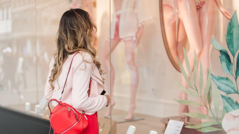 Jovem mulher bonita que olha em uma janela da loja com roupas de banho foto de stock royalty free