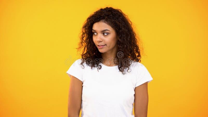 Jovem mulher bonita que olha interessada no fundo brilhante, namoradeira, curiosidade foto de stock royalty free