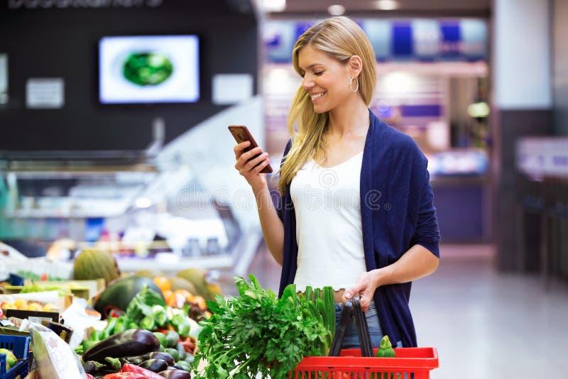 Jovem mulher bonita que olha a lista de compra no telefone celular ao comprar legumes frescos no mercado imagens de stock