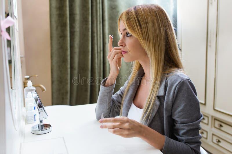 Jovem mulher bonita que põe sobre lentes de contato ao sentar-se na frente do espelho em casa imagem de stock