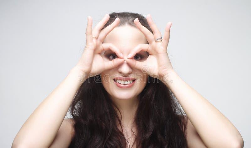 Jovem mulher bonita que procura algo com os olhos largamente abertos e fotos de stock