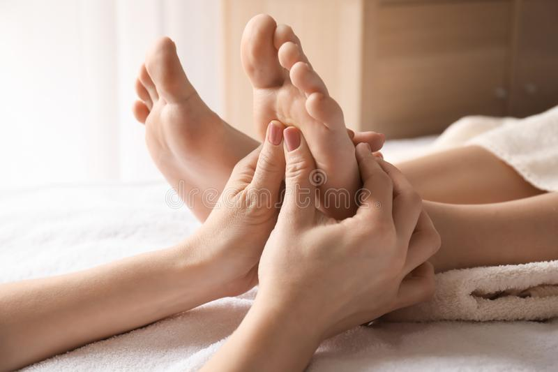 Jovem mulher bonita que recebe a massagem do pé no salão de beleza dos termas foto de stock royalty free