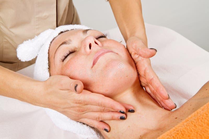 Jovem mulher bonita que recebe a massagem facial fotografia de stock