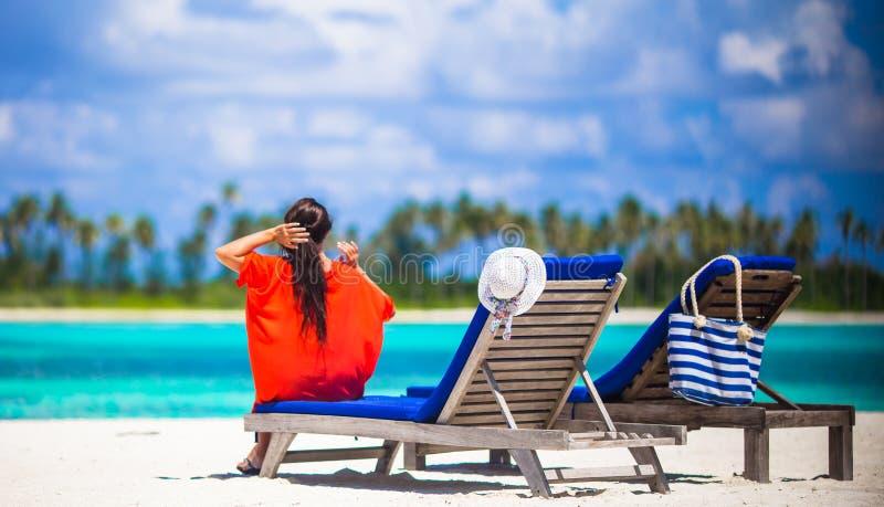 Jovem mulher bonita que relaxa em cadeiras de praia fotografia de stock royalty free