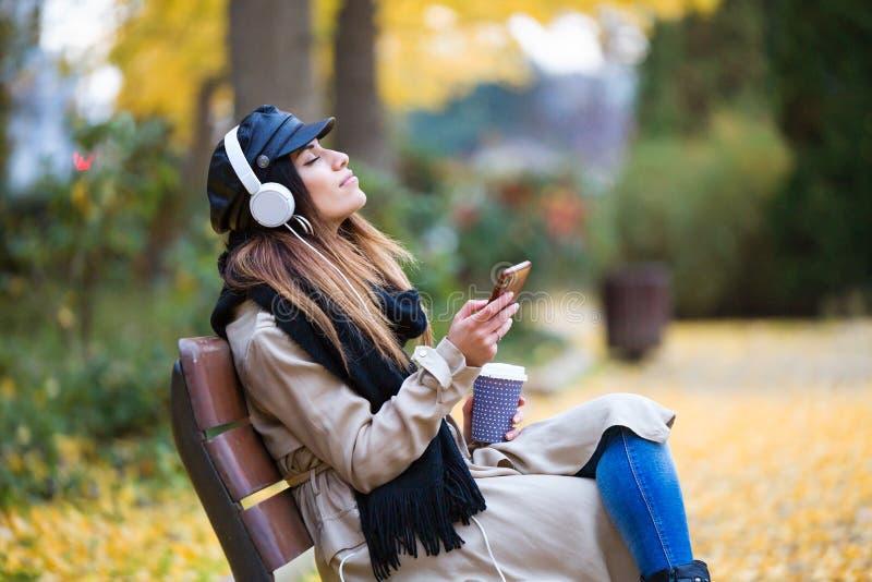Jovem mulher bonita que relaxa em um banco ao escutar a música com telefone celular no parque imagens de stock royalty free