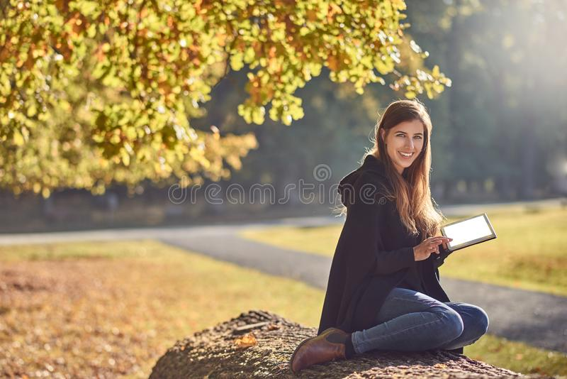 Jovem mulher bonita que relaxa em um parque do outono imagem de stock royalty free