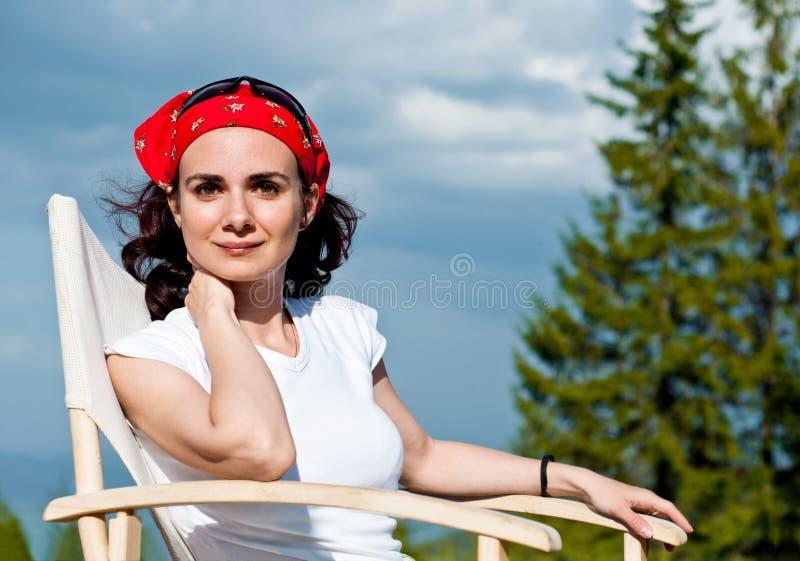 Jovem mulher bonita que relaxa em uma cadeira fotografia de stock
