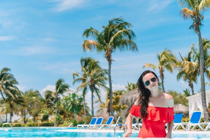Jovem mulher bonita que relaxa na piscina fotografia de stock
