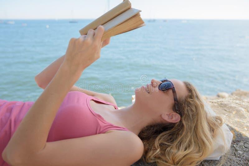 Jovem mulher bonita que relaxa na praia com livro fotografia de stock