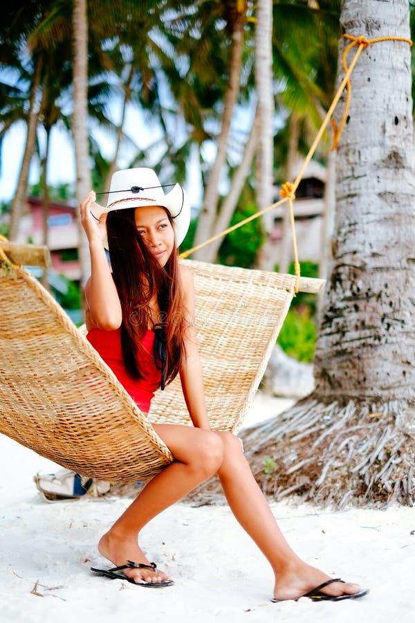 Jovem mulher bonita que relaxa na rede do rattan na praia branca da areia durante férias do curso fotografia de stock royalty free