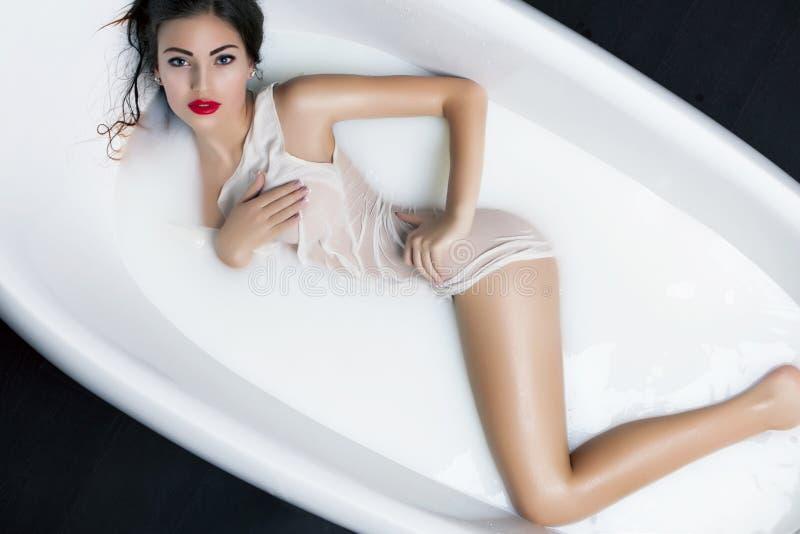 Jovem mulher bonita que relaxa no banho do leite Rejuvenescimento, pele imagem de stock royalty free