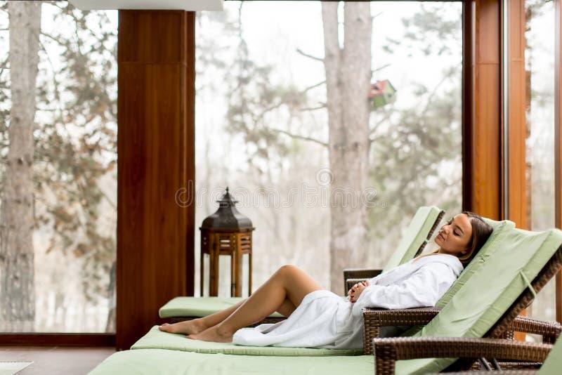 Jovem mulher bonita que relaxa no deckchair pelo poo nadador imagem de stock