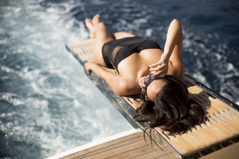 Jovem mulher bonita que relaxa no iate imagens de stock