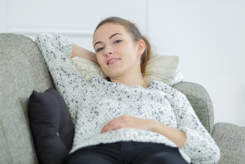 Jovem mulher bonita que relaxa no sofá em casa imagem de stock royalty free