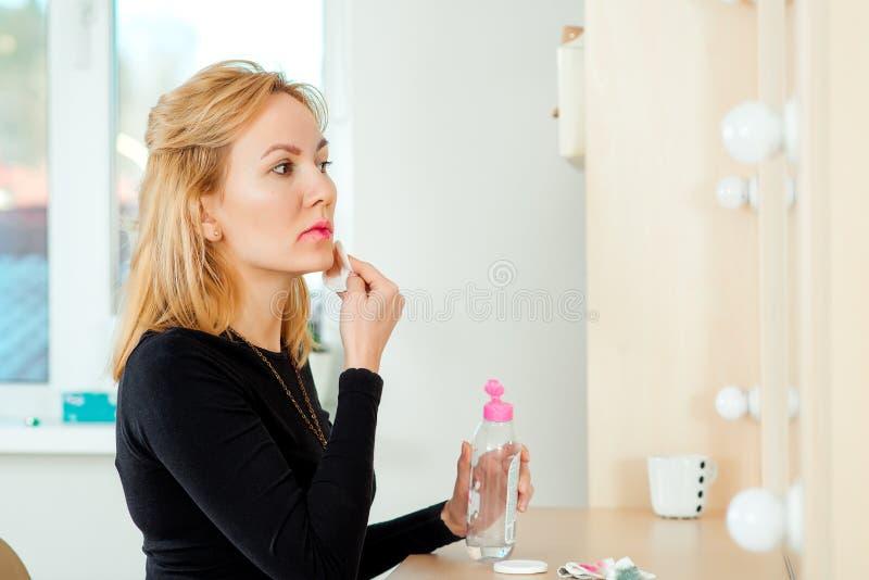Jovem mulher bonita que remove a composição de sua cara fotografia de stock royalty free