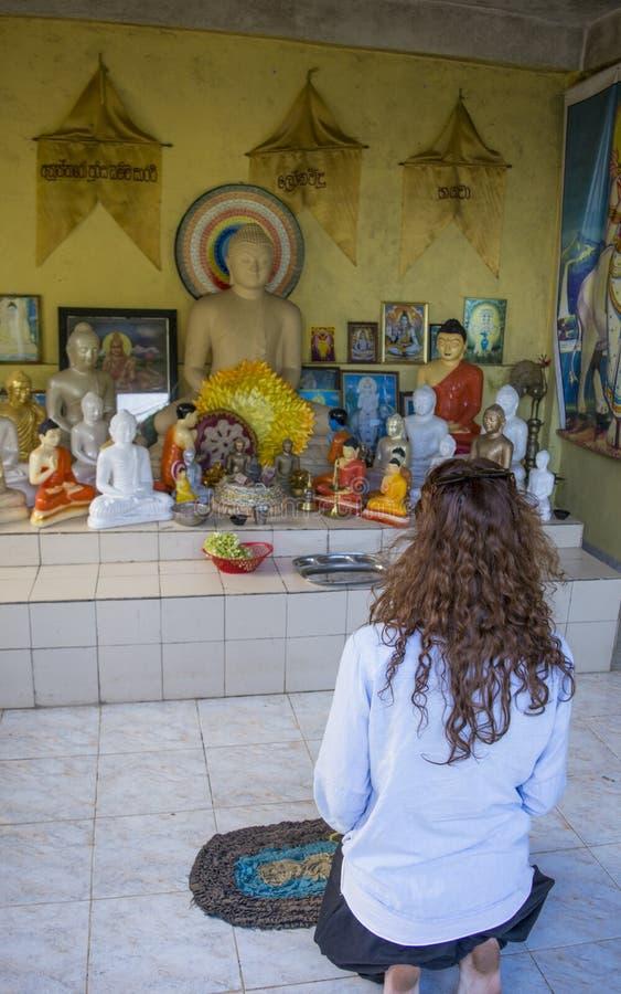 Jovem mulher bonita bonita que reza perto do altar budista foto de stock